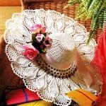 Вязаная крючком шляпка, украшенная букетиком цветов